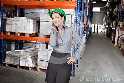 Female Supervisor Using Cell Phone At Warehouse