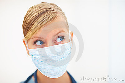 Female surgeon with face mask over white