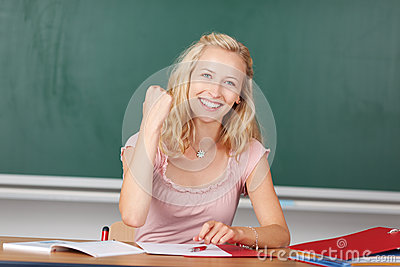Female Teacher With Clenched Fist At Desk