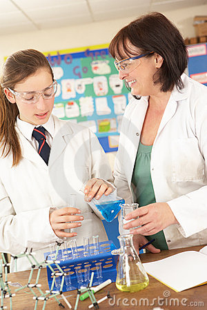 Female Teenage Student And Tutor In Science Class