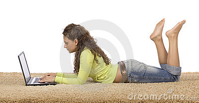 Female teenager lying on the carpet with laptop