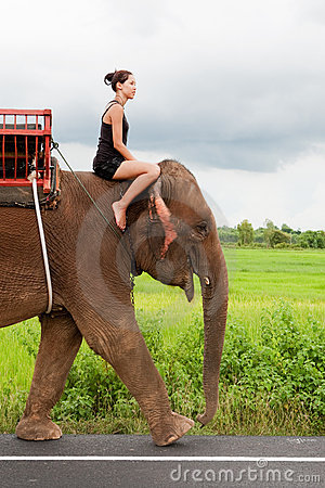 Female teenager rides elephant