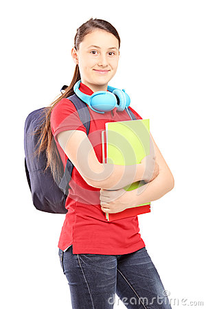 Female teenager with schoolbag and headphones holding notebooks