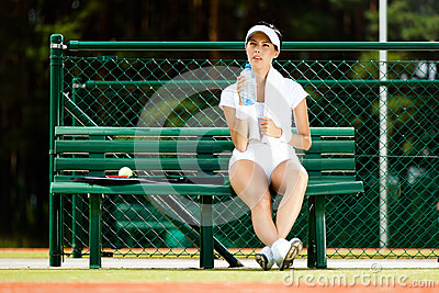 Female tennis player rests at the bench