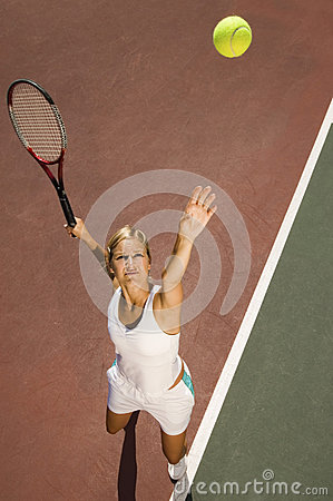Female Tennis Player Serving Ball On Court