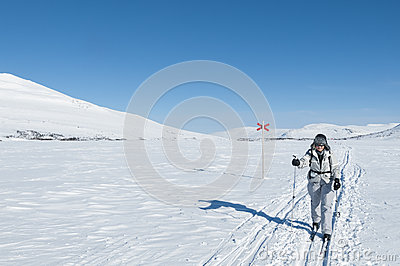 Female tour skier in backcountry ski track