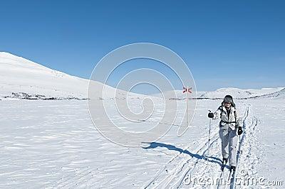 Female tour skier in backcountry ski track