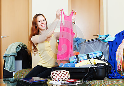 Female traveler packing suitcase at home