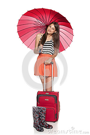Female under umbrella staning with suitcase and rubber boots