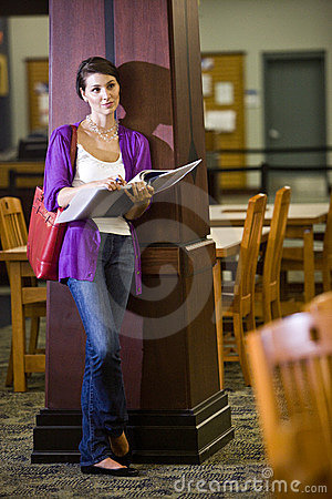 Female university student standing in library