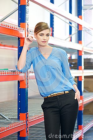Female warehouse employee standing next to shelves