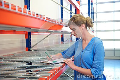 Female warehouse employee standing next to shelves and writing on clipboard