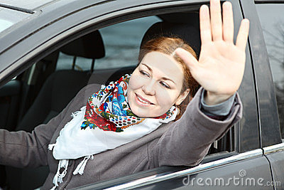 Female waving hers hand from car