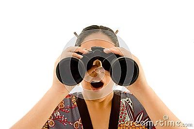 Female wearing kimono viewing through binoculars