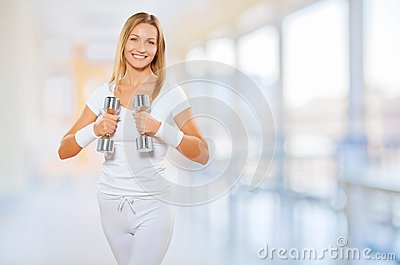 A female wearing sports clothes holding barbells