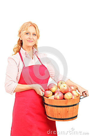 A female worker holding a basket full of apples