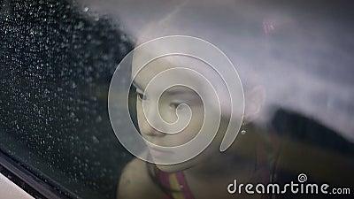 Femelle d'enfant dans la voiture en pleuvant clips vidéos