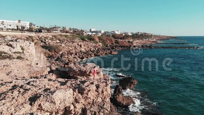 Femelle dans la robe rouge sur les falaises rocheuses avec des mains aux côtés en air Vagues fortes blanches de mer frappant le b banque de vidéos