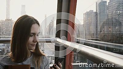 femelle 4K de touristes européenne dans la carlingue de tramway d'air Belle femme d'affaires avec le smartphone en île de New Yor clips vidéos