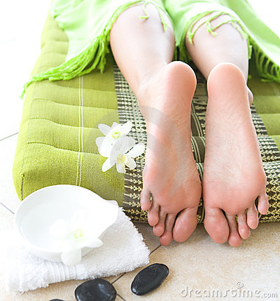 Feminine feet in spa setting with orchid