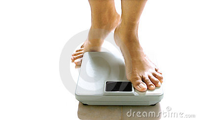 Feminine feet about to stand on a weighing scale.