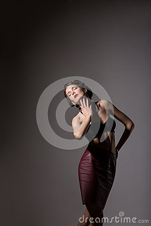 Femininity. Elegant Daydreaming Woman posing in Studio over Grey Background