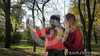 Feminitet, en ung, attraktiv flicka springer glatt för att träffa sin söta flickvän i en hatt och ta en selfig på telefon med lager videofilmer