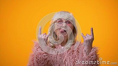 Femme agée drôle dans le manteau rose faisant des gestes de balancier et montrant la langue, amusement banque de vidéos