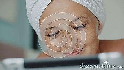 Femme allongée sur un canapé, à la recherche de serviettes de bain, sur les messages des médias sociaux banque de vidéos