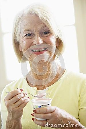 Femme aînée mangeant du yaourt
