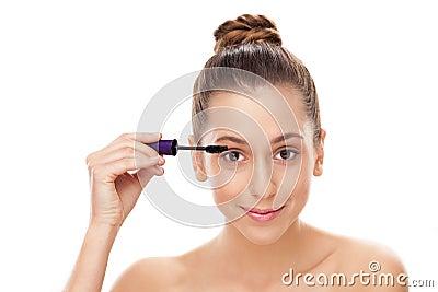 Femme appliquant le mascara