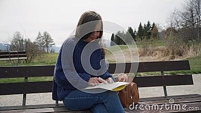 Femme assise sur un banc en bois avec une carte en papier Touriste à la recherche de la destination sur une carte papier, pointan banque de vidéos