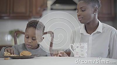 Femme attirante d'afro-am?ricain de portrait s'asseyant avec son petit fils par la table sur la cuisine Maman de relations et banque de vidéos