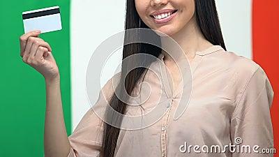 Femme attirante montrant une carte de crédit sur fond de drapeau italien, bourse d'études banque de vidéos