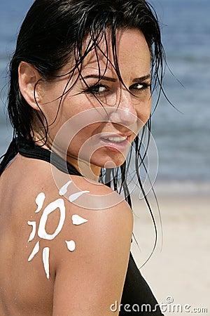 Femme avec de la crème soleil-formée du soleil