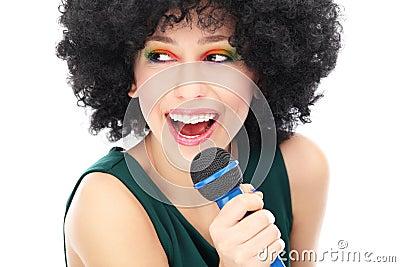 Femme avec la coiffure Afro retenant le microphone