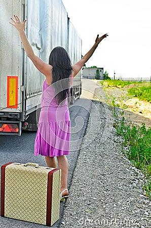 Femme avec la valise faisant de l auto-stop