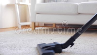 Femme avec le tapis de nettoyage d'aspirateur à la maison