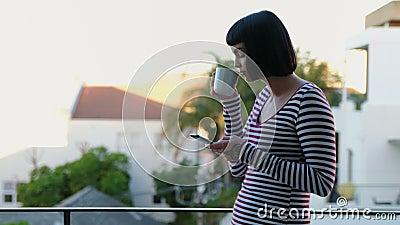 Femme ayant le café tout en à l'aide du téléphone portable dans le balcon 4k banque de vidéos