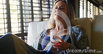 Femme ayant le vin rouge tout en regardant la télévision 4k banque de vidéos