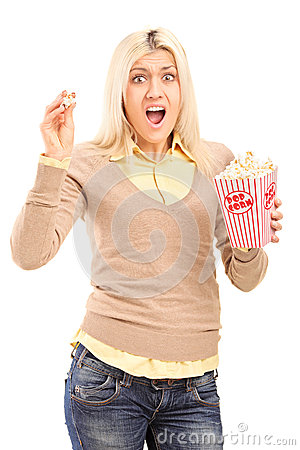 Femme blonde effrayée retenant une boîte à maïs éclaté et criant