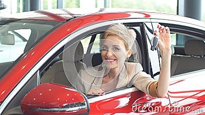 Femme comblée de conducteur souriant et montrant la nouvelle clé tout en se reposant dans la salle d'exposition de voiture banque de vidéos