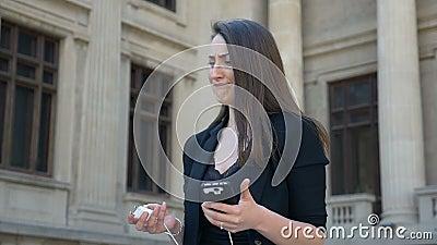 Femme d'affaires avec la basse batterie sur son smartphone se sentant nerveux au sujet de ne pas pouvoir charger clips vidéos