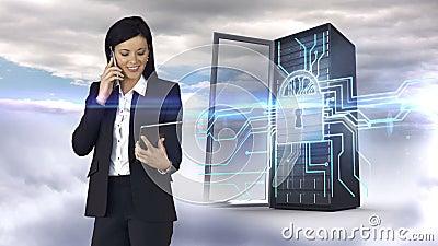 Femme d'affaires ayant l'appel téléphonique et tenant la tablette devant la tour de serveur banque de vidéos
