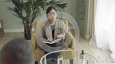 Femme d'affaires discutant avec ses clients ou collègues et prenant des notes sur le téléphone et le bloc-notes banque de vidéos