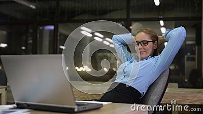 Femme d'affaires productive se penchant de retour après avoir fini le travail de bureau sur l'ordinateur portable banque de vidéos