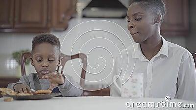 Femme d'afro-am?ricain s'asseyant avec son petit fils par la table sur la cuisine Maman et fils de relations Une famille heureuse banque de vidéos