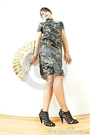 Femme dans la robe de Chinois avec le ventilateur