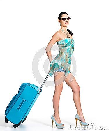 Femme de ?asual restant avec la valise de course