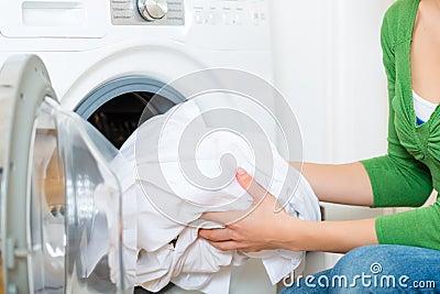 Femme de charge avec la machine à laver